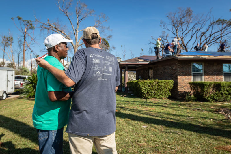 Jeremy Sprenkle, right, co-founder of The Sonder Project, visits with a Panama City homeowner
