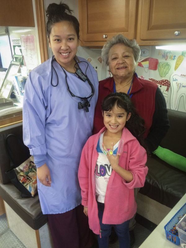 Tooth-Taxi dentist Dr. Sita Ping with a smiling patient and a volunteer.