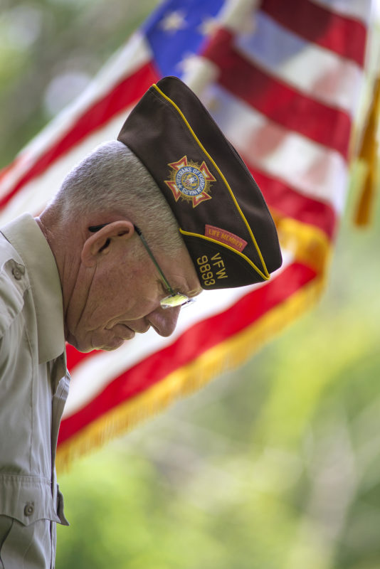 Veteran bowing his head in front of the flag.